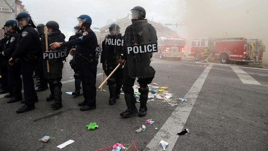 Police get in position as a store burns, Monday, April 27, 2015, during unrest following the funeral of Freddie Gray in Baltimore. Gray died from spinal injuries about a week after he was arrested and transported in a Baltimore Police Department van. (AP Photo/Patrick Semansky)