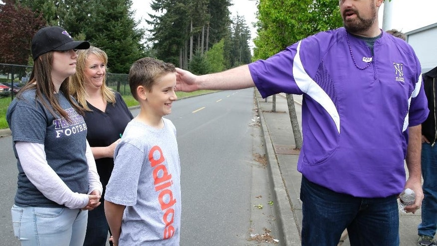Brady Olson, right, the teacher at North Thurston High School who helped subdue a student who had fired a gun in the school on Monday, points to his daughter Madelyn, 15, left, who is a student at the school as he talks to reporters Tuesday, April 28, 2015 in Lacey, Wash. Looking on are Olson's wife Shara, second from left, and their son Jake, 13. Olson said his first thoughts as he took action were to get the gun away but also to act with concern for the shooter's well-being. (AP Photo/Ted S. Warren)