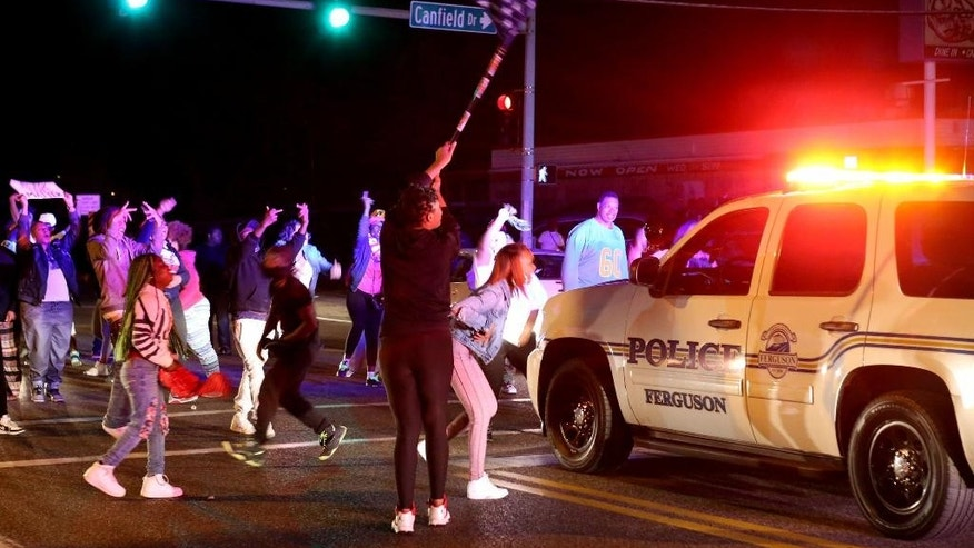 Protesters block the intersection of West Florissant Avenue and Canfield Drive in Ferguson, Mo., Tuesday night, April 28, 2015. Looting, fires and gunfire broke out overnight in Ferguson during protests in response to the death of Freddie Gray in police custody in Baltimore. (David Carson/St. Louis Post-Dispatch via AP)  EDWARDSVILLE INTELLIGENCER OUT; THE ALTON TELEGRAPH OUT; MANDATORY CREDIT