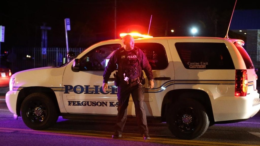 A Ferguson police officer stands on West Florissant Avenue as protesters block traffic in Ferguson, Mo., Tuesday night, April 28, 2015. Looting, fires and gunfire broke out overnight in Ferguson during protests in response to the death of Freddie Gray in police custody in Baltimore. (David Carson/St. Louis Post-Dispatch via AP)  EDWARDSVILLE INTELLIGENCER OUT; THE ALTON TELEGRAPH OUT; MANDATORY CREDIT