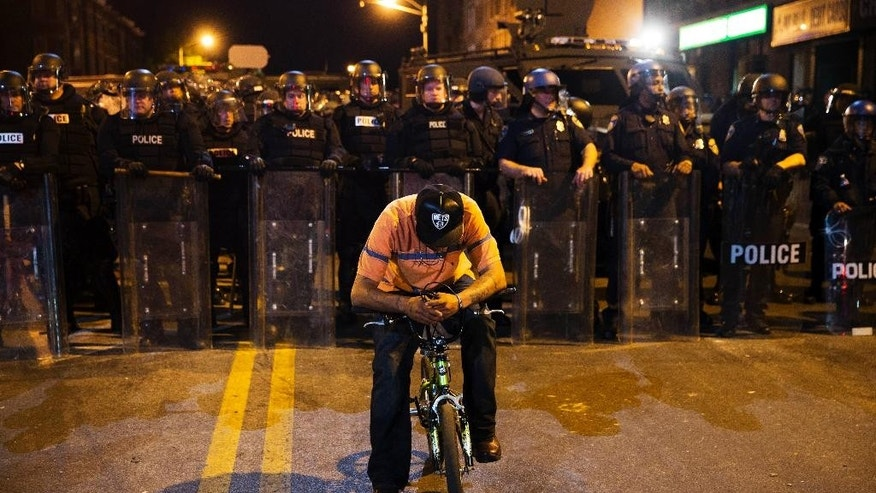 A man sits on a bicycle in front of a line of police officers in riot gear ahead of a 10 p.m. curfew in the wake of Monday's riots following the funeral for Freddie Gray, Tuesday, April 28, 2015, in Baltimore. (AP Photo/David Goldman)