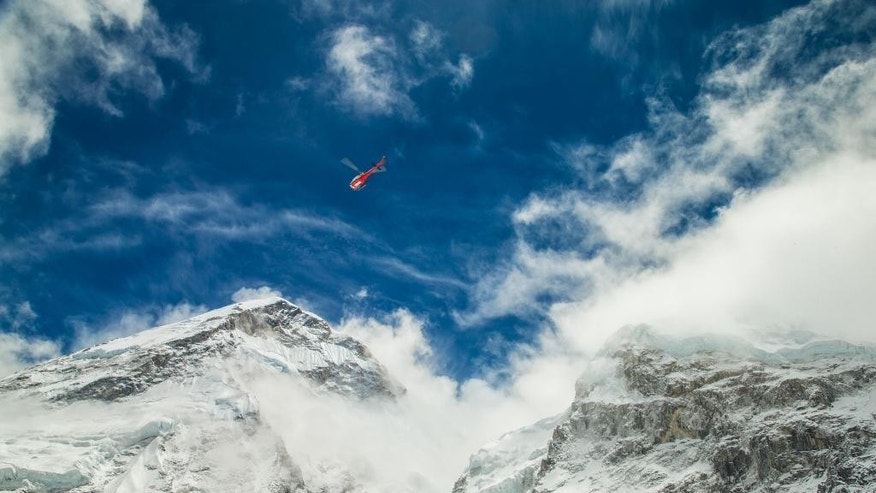 In this Sunday April 26, 2015, photo provided by 6summitschallenge.com, a helicopter prepares to rescue people at Everest Base Camp, Nepal. On Saturday, a large avalanche triggered by Nepal's massive earthquake slammed into a section of the Mount Everest mountaineering base camp, killing a number of people and left others unaccounted for. (Elia Saikaly/Courtesy of 6summitschallenge.com via AP) MANDATORY CREDIT