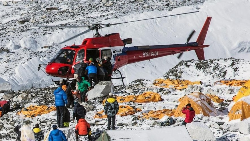 In this Sunday April 26, 2015, photo provided by 6summitschallenge.com, a helicopter prepares to rescue people at Everest Base Camp, Nepal. On Saturday, a large avalanche triggered by Nepal's massive earthquake slammed into a section of the Mount Everest mountaineering base camp, killing a number of people and left others unaccounted for. (Elia Saikaly/Courtesy of 6summitschallenge.com via AP) MANDATORY CREDIT;