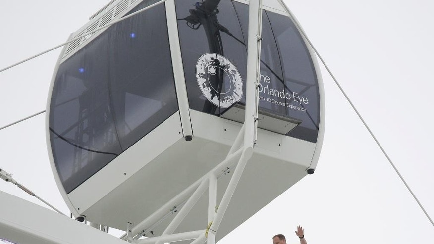 Daredevil performer Nik Wallenda walks untethered along the rim of the Orlando Eye, the city's new, 400-foot observation wheel, Wednesday, April 29, 2015, in Orlando, Fla. The walk is being done in advance of next month's public opening of the attraction. (AP Photo/John Raoux)