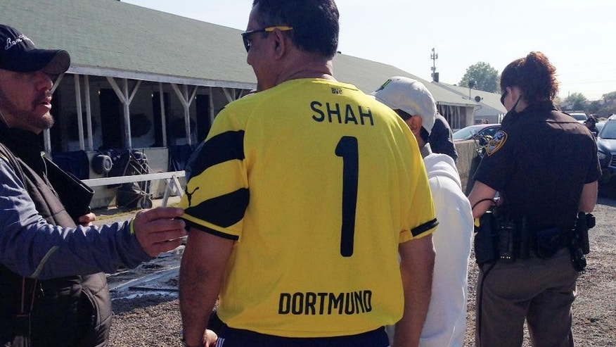 Kaleem Shah, owner of Kentucky Derby hopeful Dortmund, wears the jersey of German soccer club Borussia Dortmund, Wednesday, April 29, 2015, at Churchill Downs in Louisville, Ky. (AP Photo/Beth Harris)