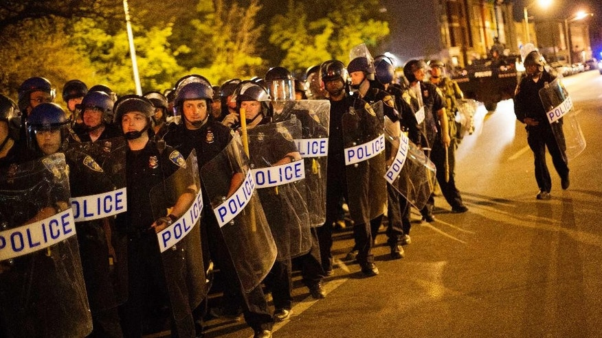Police in riot gear line up near the scene of Monday's riots ahead of a 10 p.m. curfew Wednesday, April 29, 2015, in Baltimore. The curfew was imposed after unrest in Baltimore over the death of Freddie Gray while in police custody. (AP Photo/David Goldman)