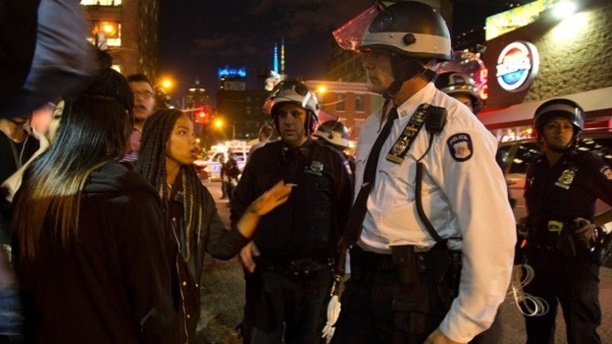 A New York City police captain listens to protesters as they demonstrate, Wednesday, April 29, 2015, in New York. Several hundred people gathered in New York on Wednesday to protest the death of Freddie Gray, a Baltimore man who was critically injured in police custody, and more than a dozen were arrested. (AP Photo/Julie Jacobson)