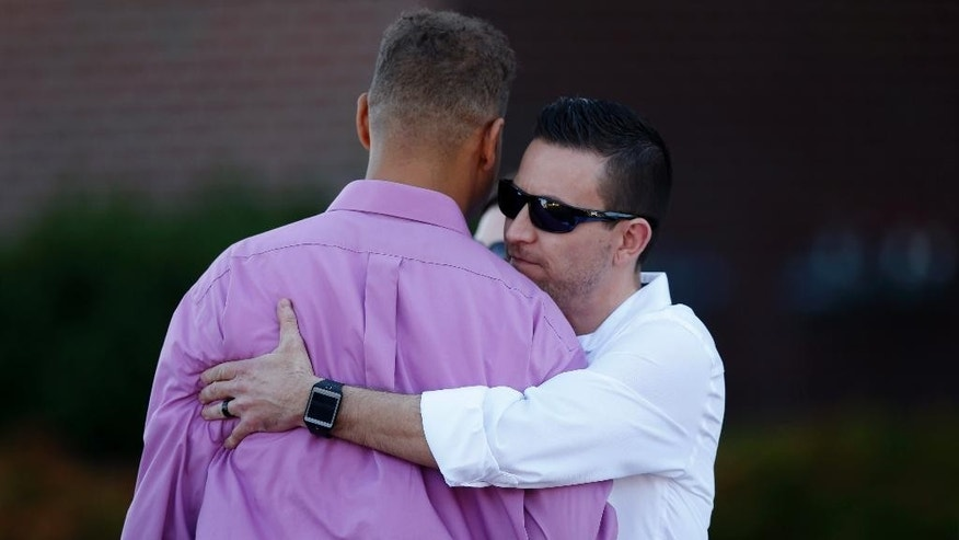 Marcus Weaver, left, a victim of the 2012 shooting at an Aurora, Colo., movie theater, is embraced after Weaver testified during the third day in the trial of James Holmes, Wednesday, April 29, 2015, in Centennial, Colo. Holmes is charged with multiple counts of murder and attempted murder in an attack that killed 12 people and injured 70. (AP Photo/David Zalubowski)