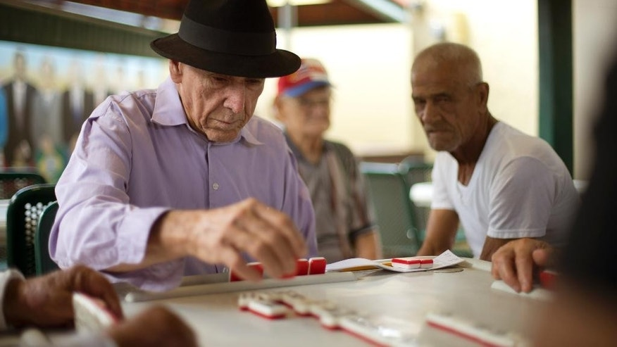 FILE - In this May 2, 2014, file photo, men play dominoes on Calle Ocho (Eighth Street) in Miami's Little Havana.  If South Florida seceded, almost three-quarters of Original Florida's population would be non-Hispanic white, compared to around half in South Florida. Hispanics would make up almost 30 percent of South Florida's population. (AP Photo/J Pat Carter, File)