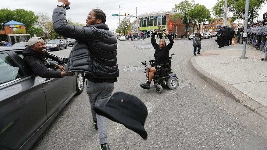 Donta Allen, center, loses his hat while celebrating with a passing motorist at left and Lisa Mills, right, in the intersection where some of Monday's riots occurred on Friday, May 1, 2015, after State's Attorney Marilyn J. Mosby announced criminal charges against all six officers suspended after Freddie Gray suffered a fatal spinal injury while in police custody in Baltimore.  Mosby announced the stiffest charge, second-degree depraved heart murder, against the driver of the police van. Other officers faced charges of involuntary manslaughter, assault and illegal arrest. (AP Photo/David Goldman)