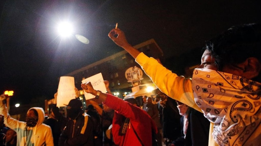Protesters raise their hands as a circling police helicopter illuminates the area on the third night of curfew, Thursday, April 30, 2015, in Baltimore. (AP Photo/Alex Brandon)