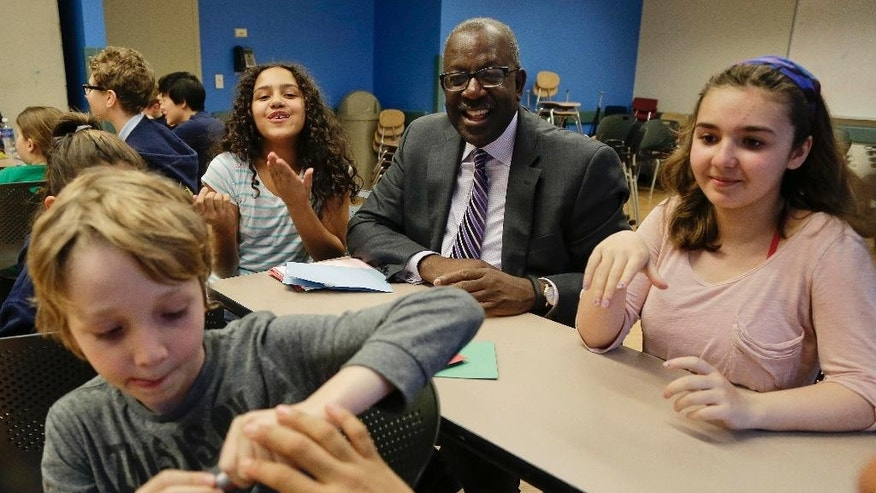 Kevin Washington, center, president and CEO of the YMCA of the USA, participates in a math game being played by young teens at the McBurney YMCA during an open after-school program called The Zone, Wednesday, April 22, 2015, in New York. Washington was installed as president and CEO in February and oversees 900 locally run associations which operate a total of 2,700 branches serving about 9 million youth and 13 million adults in communities ranging from affluent suburbs to hard-up inner-city districts. (AP Photo/Julie Jacobson)