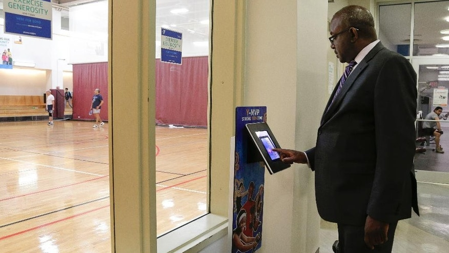 Kevin Washington, president and CEO of the YMCA of the USA, examines the Y-MVP teen fitness program on one of the many digital displays at the McBurney YMCA facility in Lower Manhattan, Wednesday, April 22, 2015, in New York. Washington was installed as president and CEO in February and oversees 900 locally run associations which operate a total of 2,700 branches serving about 9 million youth and 13 million adults in communities ranging from affluent suburbs to hard-up inner-city districts. (AP Photo/Julie Jacobson)