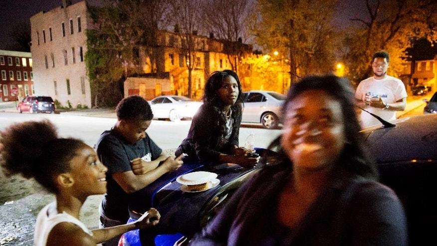 People gather during a party at a housing complex where Freddie Gray was arrested as a six day curfew was lifted Sunday, May 3, 2015, in Baltimore. (AP Photo/David Goldman)