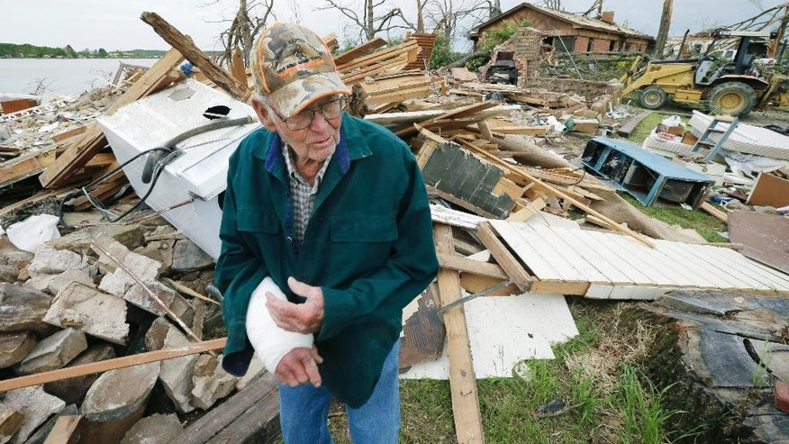 FILE - In this April 29, 2014 file photo, Louie Short walks through rubble that is all that remains of his Mayflower, Ark., home. Short's arm was injured in a tornado that struck his neighborhood killing one man. Forecasters who are troubled by the high death count from twisters in recent years say they must find better ways to communicate if the public is going to behave appropriately as bad weather approaches. (AP Photo/Danny Johnston, File)