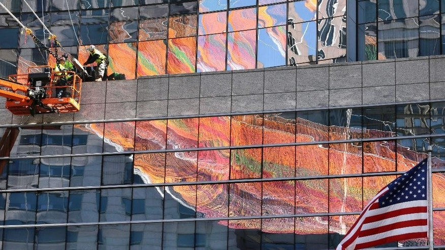Workers, top left, secure lines that support a 600-foot sculpture, a portion of which is reflected in glass on a building, as it is suspended between high-rise buildings, Sunday, May 3, 2015, in Boston. The sculpture, that is to remain in place through October 2015, is made from over 100 miles of twine and utilizes over half a million knots in its construction. (AP Photo/Steven Senne)