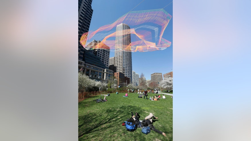 Lushik Wahba, bottom center, and Nare Filiposyan, bottom right, both of Bennington, Vt., look toward a colorful 600-foot sculpture suspended between high-rise buildings above the Rose Kennedy Greenway, Sunday, May 3, 2015, in Boston. The sculpture, that is to remain in place through October 2015, is made from over 100 miles of twine and utilizes over half a million knots. (AP Photo/Steven Senne)