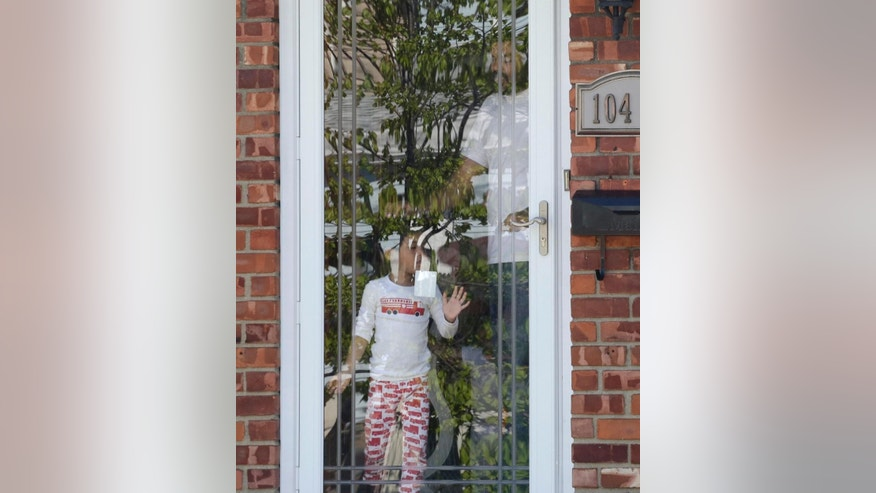 A man and girl stand behind a glass door of a house, Sunday, May 3, 2015, as they watch police investigate the nearby scene of a shooting in the Queens borough of New York. Demetrius Blackwell is accused of shooting a New York City police officer in the head Saturday evening and is being charged with two counts of attempted murder of a police officer. (AP Photo/Mark Lennihan)