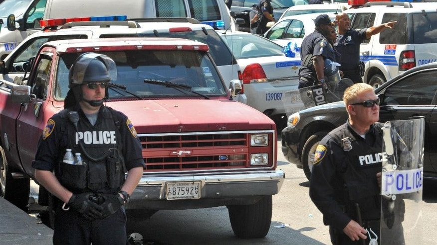 Police stand behind tape Monday, May 4, 2015, in Baltimore. Lt. Col. Melvin Russell said police pursued a man who was spotted on surveillance cameras and appeared to be armed with a handgun. Police said the man was taken into custody after a brief chase, during which a gunshot was heard. (Amy Davis/The Baltimore Sun via AP)
