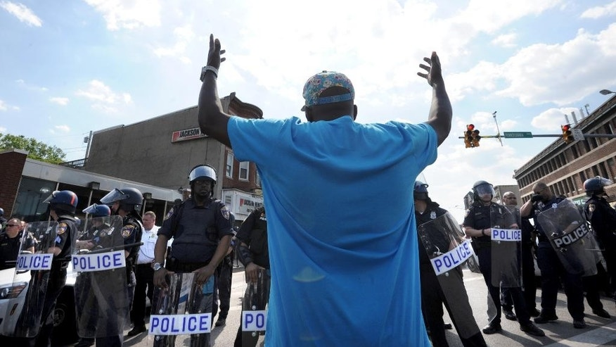 A man raises his arms near a line of police Monday, May 4, 2015, in Baltimore. Lt. Col. Melvin Russell said police pursued a man who was spotted on surveillance cameras and appeared to be armed with a handgun. Police said the man was taken into custody after a brief chase, during which a gunshot was heard. (Algerina Perna/The Baltimore Sun via AP)