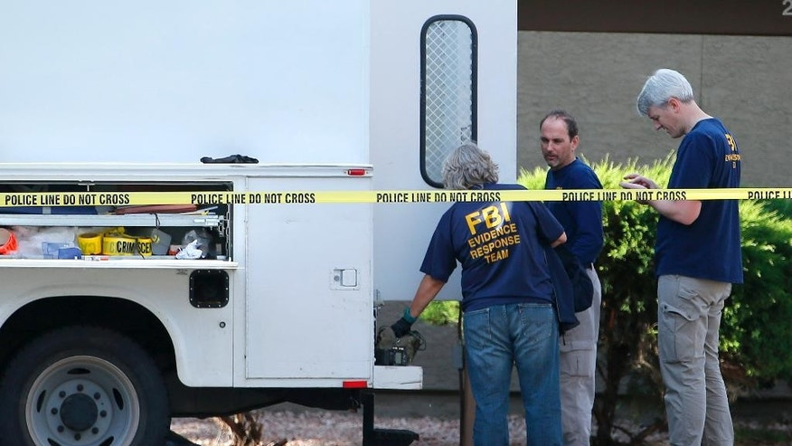 FBI investigators stand near an apartment being searched Monday, May 4, 2015, in Phoenix, believed to be the home of one of two gunmen who were shot and killed the night before outside a venue hosting an exhibit about the Prophet Muhammad in suburban Dallas. Garland, Texas, police officer Joe Harn says the men had opened fire with assault rifles, and that one officer had fatally shot both gunmen.   (AP Photo/Ross D. Franklin)