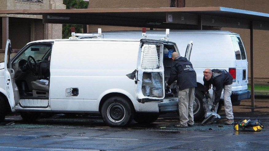 FBI investigators search a vehicle, Monday, May 4, 2015, in Phoenix, believed to belong to one of two gunmen who were shot and killed the night before outside a venue hosting an exhibit about the Prophet Muhammad in suburban Dallas. Garland, Texas, police officer Joe Harn says the men had opened fire with assault rifles, and that one officer had fatally shot both gunmen.   (AP Photo/Brian Skoloff)