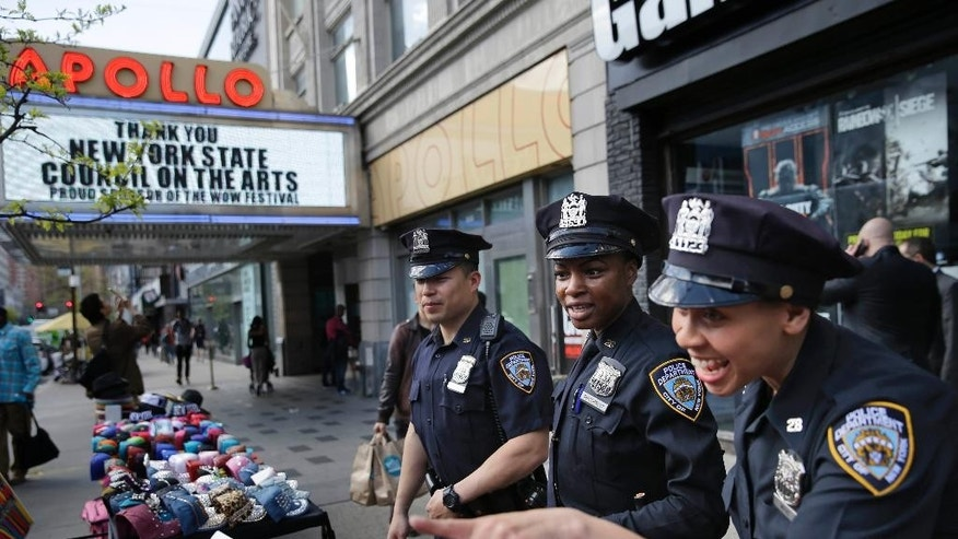 Police officers Lanora Moore, right, Shakara President, center, and Max Chow talk with a vendor on 125th Street in the Harlem section of New York, Wednesday, April 29, 2015. (AP Photo/Seth Wenig)