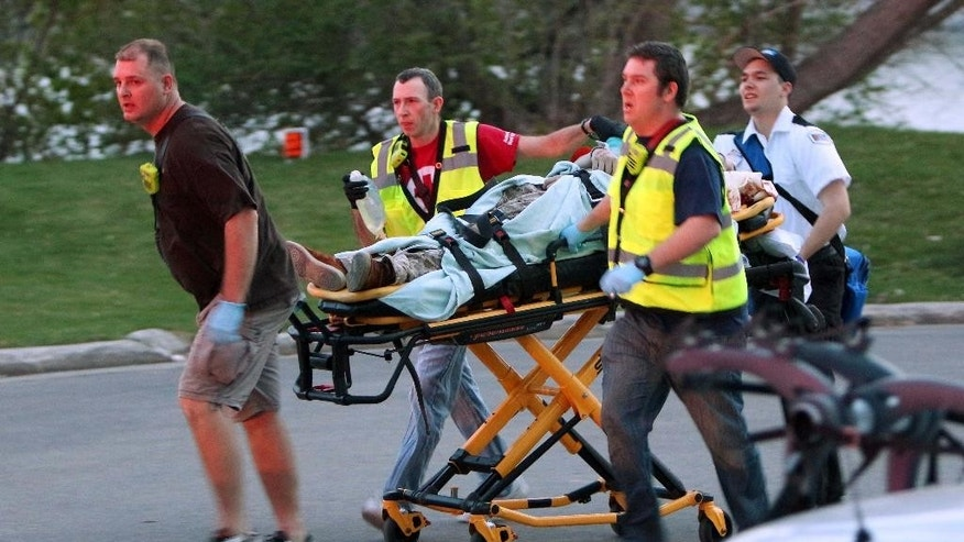 In this May 3, 2015 photo, authorities move Sergio Valencia del Toro, 27, to an ambulance following a shooting at a recreational bridge in the City of Menasha, Wis. Police say del Toro and his fiancee had recently called off their wedding and had argued before del Toto randomly shot four strangers before killing himself. Authorities say four are dead and one hospitalized in critical condition. (Duke Behnke/The Post-Crescent  via AP)