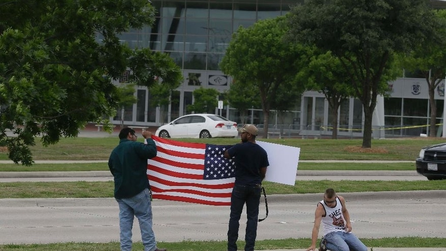 Raheem Peters, let, and Joseph Offutt, center, hold a sign and a U.S. flag as Conner McCasland, kneeling, makes a poster across the street from the Curtis Culwell Center, Tuesday, May 5, 2015, in Garland, Texas. A man, whose social media presence was being scrutinized by federal authorities, was one of two suspects killed in the Sunday shooting at this location that hosted a cartoon contest featuring images of the Muslim Prophet Muhammad. The Islamic State group on Tuesday claimed responsibility for the attack. (AP Photo/LM Otero)