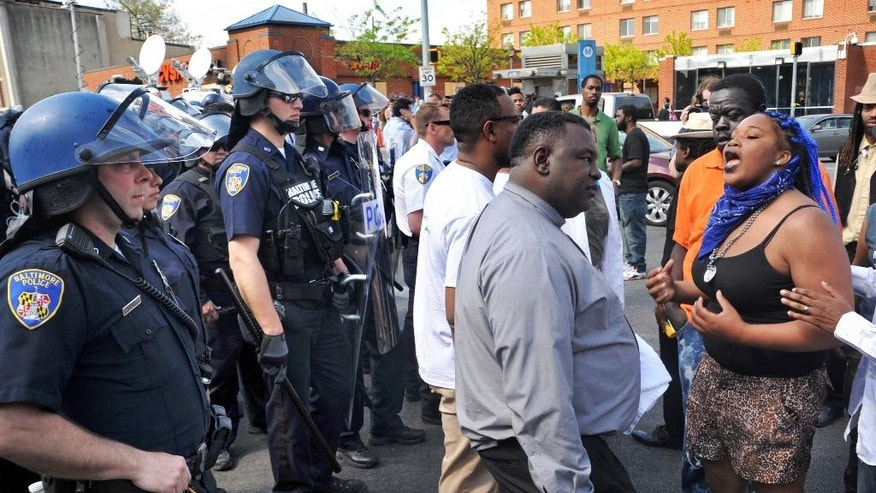 Protesters chant in front of police Monday, May 4, 2015, in Baltimore. Lt. Col. Melvin Russell said police pursued a man who was spotted on surveillance cameras and appeared to be armed with a handgun. Police said the man was taken into custody after a brief chase, during which a gunshot was heard. (Amy Davis/The Baltimore Sun via AP)