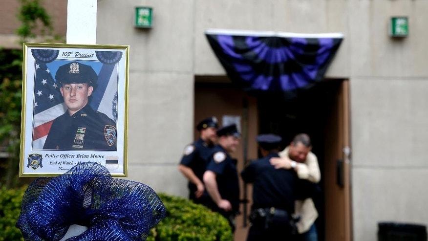 A picture of Brian Moore is displayed in front of his precinct house in the Queens section of New York, Tuesday, May 5, 2015.  The 25-year-old Moore died Monday, two days after he was shot. He had been in a coma after undergoing brain surgery.  Demetrius Blackwell will be charged with first-degree murder, prosecutors said. He was charged earlier with attempted murder and other crimes. He is being held without bail and has not entered a plea. (AP Photo/Seth Wenig)