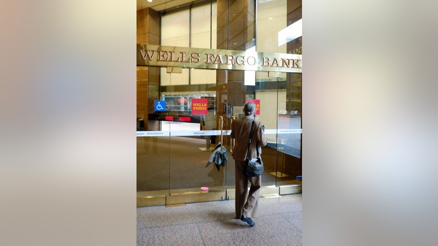 A customer arrives at a Wells Fargo Bank branch in downtown Los Angeles on Tuesday, May 5, 2015. The city of Los Angeles is suing Wells Fargo Bank, alleging that employees driven by strict sales pressure opened unauthorized accounts for customers that charged them fees and damaged their credit. (AP Photo/Richard Vogel)