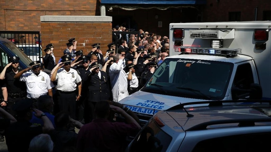 Police officers salute as the body of Brian Moore as it leaves Jamaica Hospital in New York, Monday, May 4, 2015. Moore, a 25-year-old police officer shot in the head over the weekend while attempting to stop a man suspected of carrying a handgun, has died from his injuries, the third New York Police Department officer slain in the line-of-duty in five months, a City Hall official said Monday. (AP Photo/Seth Wenig)