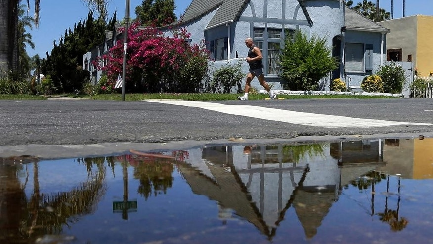FILE - In this July 9, 2014, file photo, a house is reflected in a puddle of water from an irrigated front yard in San Diego. Californians conserved little water in March and local officials were not aggressive in cracking down on waste, state regulators reported Tuesday, May 5, 2015 as they considered tough measures to force savings amid a continuing drought. (AP Photo/Gregory Bull, File)