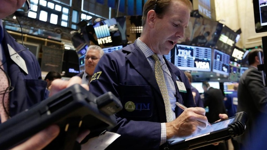 Trader Michael Smyth, right, works on the floor of the New York Stock Exchange Tuesday, May 5, 2015. Stocks are little changed in early trading following two days of gains that brought the market close to a record high. (AP Photo/Richard Drew)