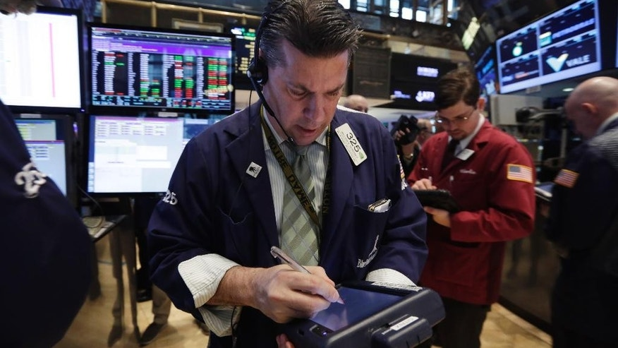 Trader William McInenery, center, works on the floor of the New York Stock Exchange Tuesday, May 5, 2015. Stocks are little changed in early trading following two days of gains that brought the market close to a record high. (AP Photo/Richard Drew)