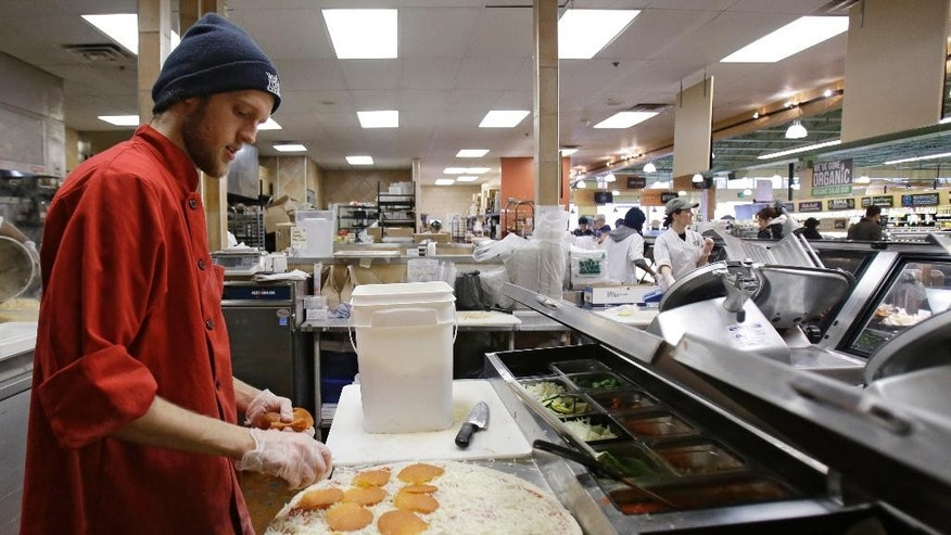 In this Thursday, March 27, 2014 John Pittenger makes a pepperoni pizza at the Whole Foods Market in Woodmere Village, Ohio. The Institute for Supply Management releases its service sector index for April 2015 on Tuesday, May 5, 2015. (AP Photo/Tony Dejak)