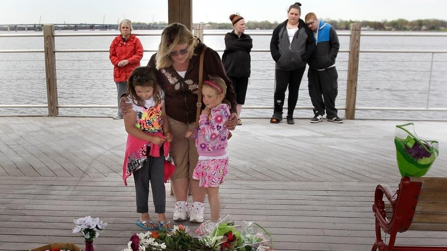 Heather, left, Christy and Caitlyn Betley  pause to pray after placing flowers at a memorial in the pavilion on the re-opened Trestle Trail near Fritse Park, on Tuesday May 5, 2015 in the Town of Menasha, Wis. A shooting spree that resulted in four fatalities and one person injured occurred on the Fox Cities Trestle Trail bridge in Menasha Sunday night May 3, 2015 in Menasha, Wis. (Wm.Glasheen/The Post-Crescent via AP) NO SALES
