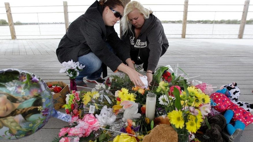 Jodi Meyer, left, and Sonia Meyer place flowers at a memorial in the pavilion on the re-opened Trestle Trail, on the east side of the trail near Fritse Park, Tuesday May 5, 2015 in the Town of Menasha, Wis. A shooting spree that resulted in four fatalities and one person injured occurred on the Fox Cities Trestle Trail bridge in Menasha Sunday night May 3, 2015 in Menasha, Wis. (Wm.Glasheen/The Post-Crescent via AP) NO SALES