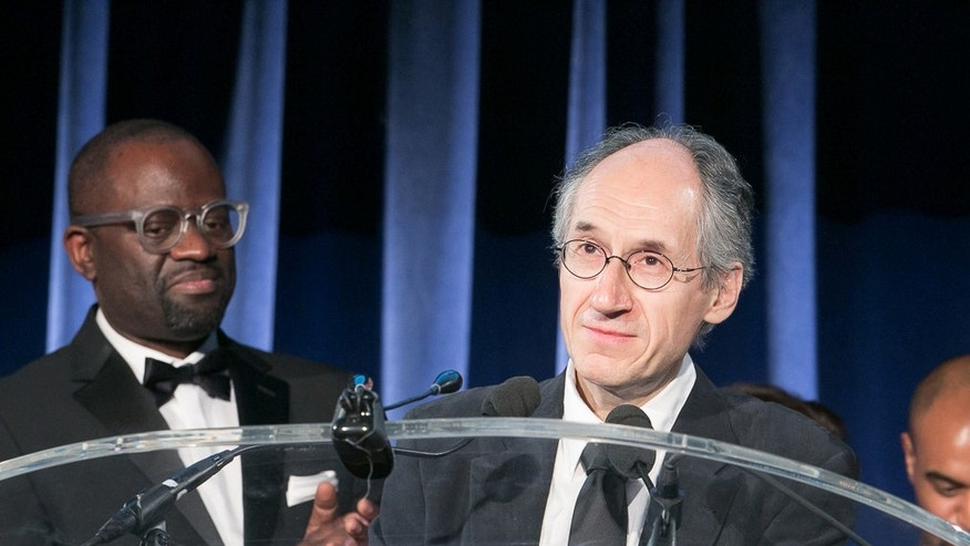 In this May 5, 2015 photo released by the PEN American Center, Charlie Hebdo Editor-in-Chief  Gerard Biard accepts the Freedom of Expression Courage Award  as Alain Mabanckou,, left, looks on during the 2015 PEN Gala at the American Museum of Natural History in New York. (Beowulf Sheehan/PEN American Center via AP)