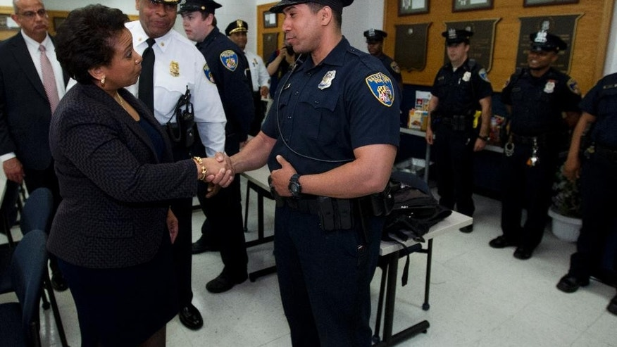 Attorney General Loretta Lynch, left, shake hands with Baltimore police officers during a visit to the Central District of Baltimore Police Department , on Tuesday, May 5, 2015, in Baltimore Md. Lynch pledged Tuesday to improve the city's police department after meeting with the family of a man who was fatally injured in police custody. (AP Photo/Jose Luis Magana, Pool)