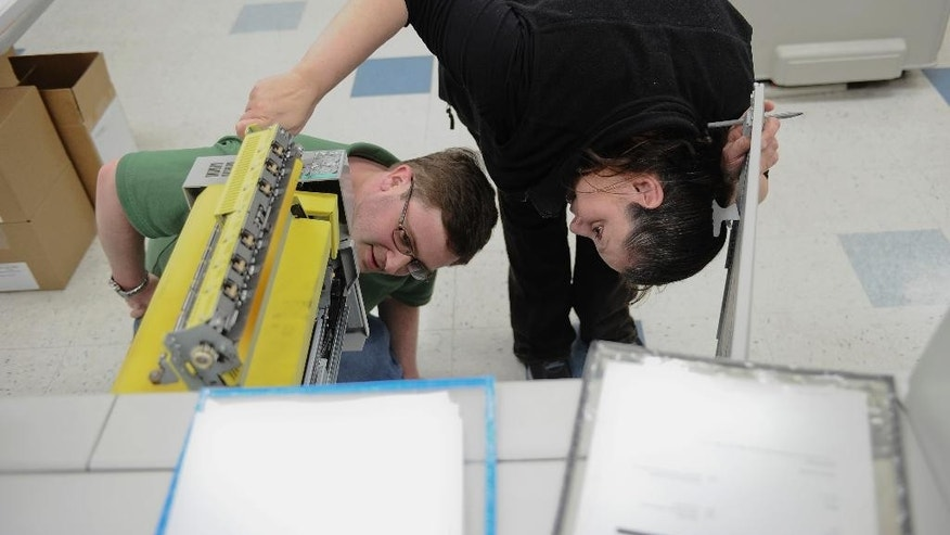 In this Wednesday, April 1, 2015 photo, Bill Lewis, left, and colleague Rosie Rivera inspect a copy machine at CMS Mailing, in Monroe, Conn. Lewis was hired by CMS Mailing through Platform To Employment, a nonprofit program that offers to pay some long-term unemployed workers' salaries for their first 8 weeks on a new job, essentially eliminating the companies' risk of hiring of them. (AP Photo/Jessica Hill)