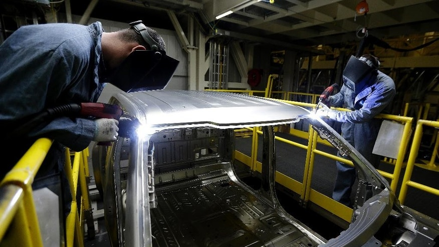 In this March 13, 2015 photo, workers weld body panels on the new aluminum-alloy body Ford F-150 truck at the company's Kansas City Assembly Plant in Claycomo, Mo. The Labor Department releases first-quarter productivity data on Wednesday, May 6, 2015. (AP Photo/Charlie Riedel)