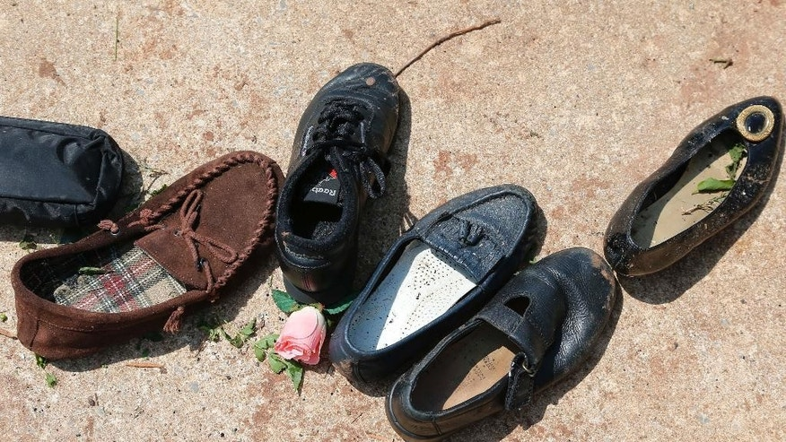 Mismatched shoes are lined up after being salvaged from a ruined recreational vehicle in Oklahoma City, Thursday, May 7, 2015. Gov. Mary Fallin has declared a state of emergency in 12 Oklahoma counties hit by tornadoes, severe storms, straight-line winds and flooding on Wednesday. (AP Photo/Sue Ogrocki)