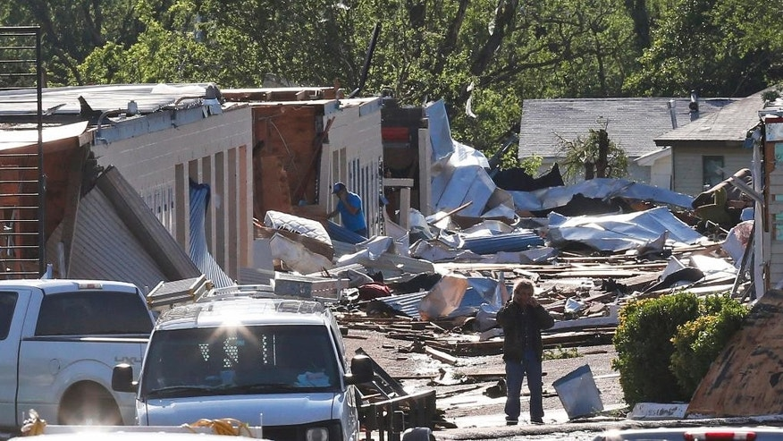 People look through rubble, Thursday, May 7, 2015, in an area damaged by severe weather a day earlier, in Oklahoma City. Authorities are assessing the damage from spring storms that spawned more than a dozen suspected tornadoes in the southern Plains, destroying dozens of homes, causing flooding and forcing the evacuation of Oklahoma City's main airport. At least 12 people were injured but there were no reports of deaths. (AP Photo/Sue Ogrocki)
