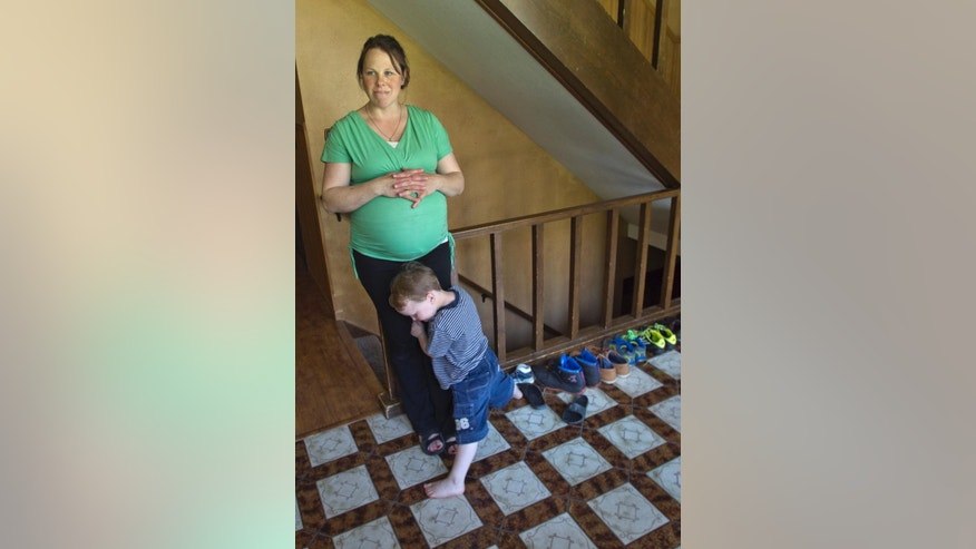 Kateri Schwandt shares a moment with her son, Luke, 3, inside their Rockford, Mich., home Wednesday, May 6, 2015. Schwandt and her husband, Jay, have 12 boys. They are expecting a baby on May 9, the day before Mother's Day, and they're sticking to their tradition of not finding out in advance whether they're having a boy or girl. (Chris Clark/The Grand Rapids Press via AP) ALL LOCAL TELEVISION OUT; LOCAL TELEVISION INTERNET OUT