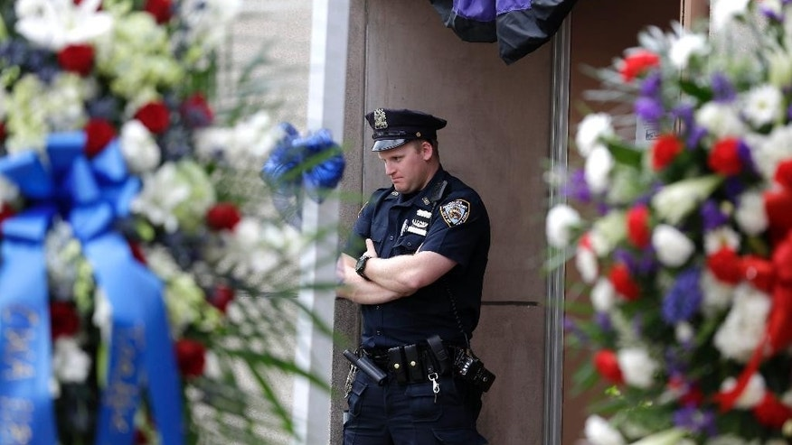 A police officer stands under bunting in front of the 105th precinct house in the Queens section of New York, Tuesday, May 5, 2015. Officer Brian Moore died Monday, two days after he was shot. He had been in a coma after undergoing brain surgery. Demetrius Blackwell will be charged with first-degree murder, prosecutors said. He was charged earlier with attempted murder and other crimes. He is being held without bail and has not entered a plea. (AP Photo/Seth Wenig)