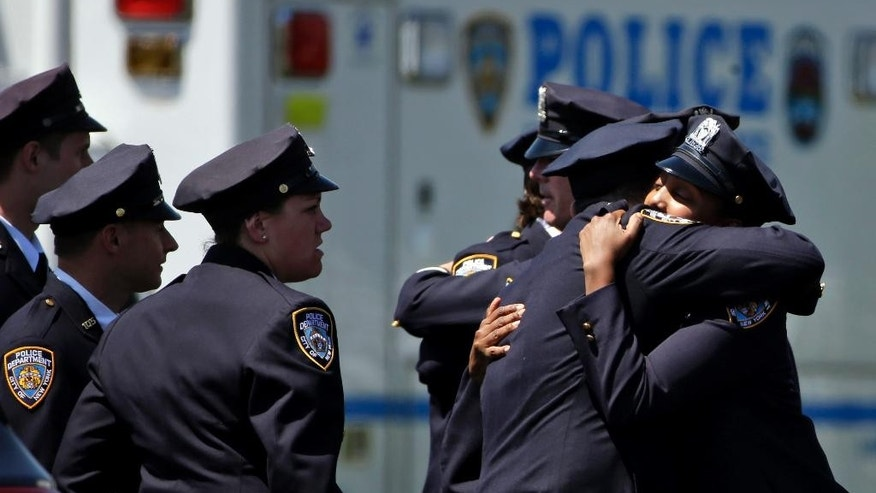 Police officers embrace before entering the wake for New York City police officer Brian Moore, Thursday, May 7, 2015,  in Bethpage, N.Y. Moore died Monday after being shot in the head while on duty last Saturday. The 25-year-old and his partner had stopped a man suspected of carrying a handgun when the man opened fire on them. (AP Photo/Seth Wenig)