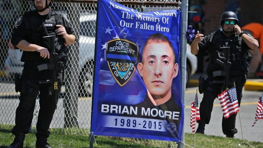 Heavily armed police officers stand near a sign during the wake for New York City police officer Brian Moore Thursday, May 7, 2015,  in Bethpage, N.Y. Moore died Monday after being shot in the head while on duty last Saturday. The 25-year-old and his partner had stopped a man suspected of carrying a handgun when the man opened fire on them. (AP Photo/Seth Wenig)
