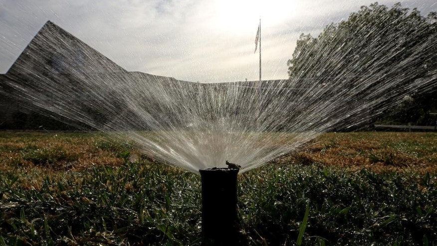 FILE - In this July 15, 2014, file photo, sprinklers water a lawn in Sacramento, Calif. Most Californians have heard by now that they should stop watering their lawns to save water in the drought. But there are smaller steps to take, too, from taking shorter showers and doing less laundry to restaurants skipping water at tables. (AP Photo/Rich Pedroncelli, File)